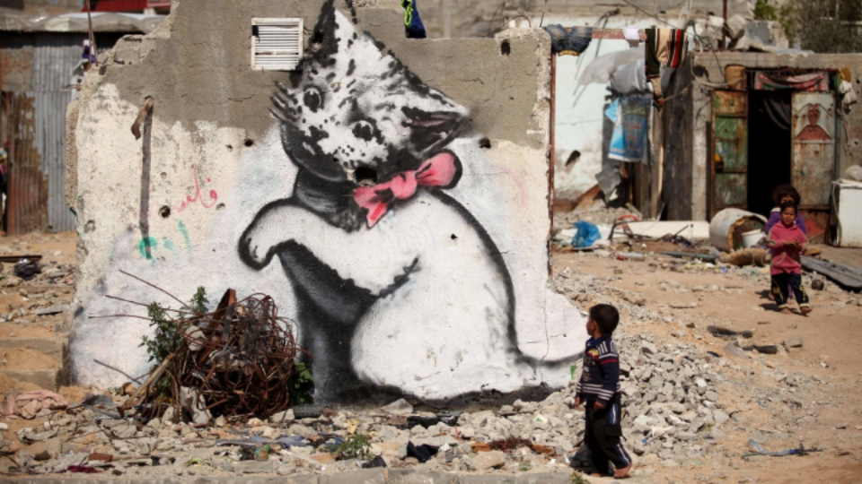 In Gaza, a 10-foot-tall kitten plays with a ball of barbed wire, courtesy of Banksy. Photo: Al Jazeera English.