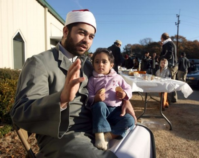 Mustafa Khattab, the Egyptian-born imam of the Islamic Society of Clemson (South Carolina), holding his daughter in 2008. That same year, I interviewed Mustafa. Photo: Nathan F. Elmore.