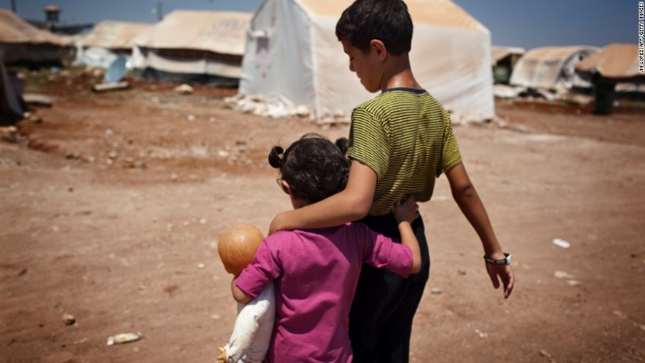 A brother and sister walk the streets of a refugee camp inside Syria. Photo: J.M. Lopez/AFP/Getty Images.