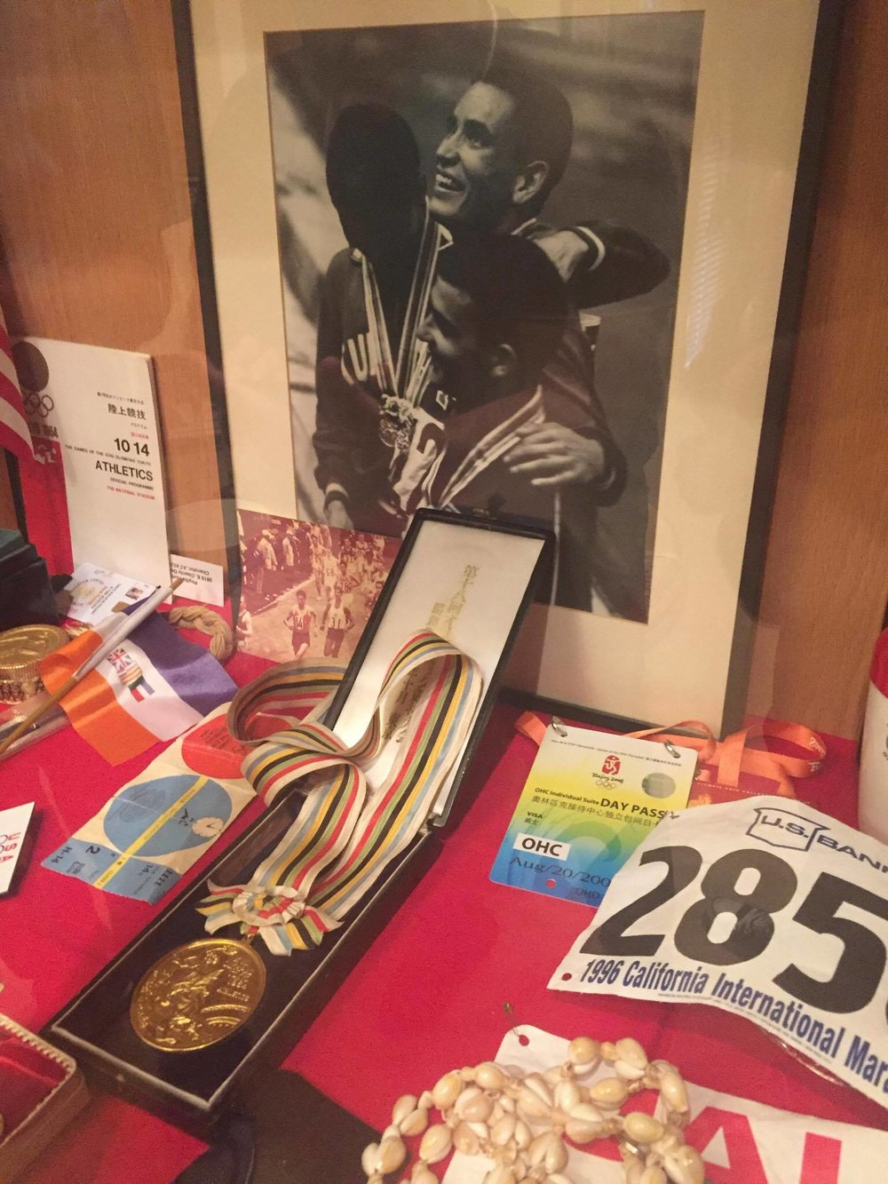 Billy Mills's 1964 Olympic Medal, alongside other running memorabilia from over the years. Use of this photograph courtesy of Dominic Mills, Billy's grandson and current medal owner.