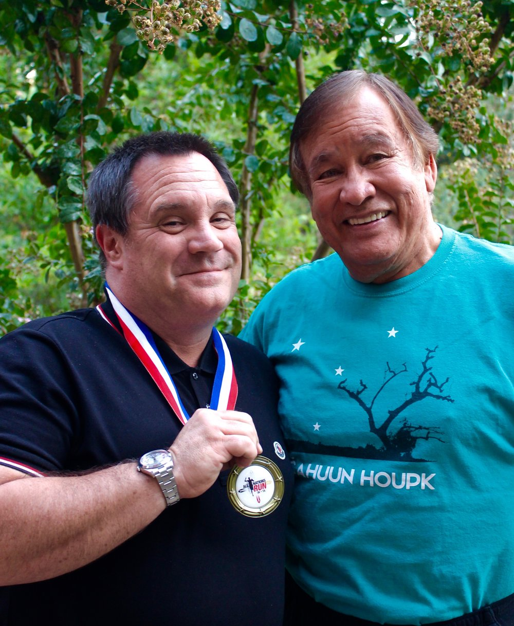 "Michael Glascock (left) and Billy Mills (right). Michael has attended the All Nations Run in previous years, and here he proudly shows off the gold medal he won in the ""Best Striped Shirt"" category. Click  here  to register for Saturday's race!"