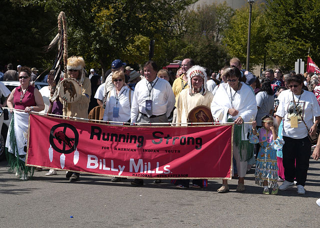 Pat (center, left) and Billy Mills (center, right) march in 2004 alongside Running Strong and other organizations to celebrate the opening of the National Museum of the American Indian. Photo by  Bill Koplitz