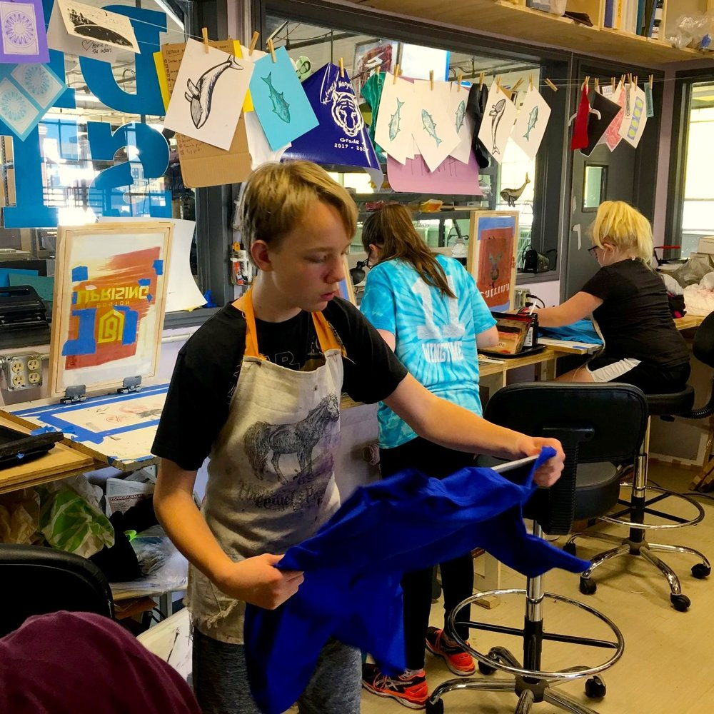 Students work with screens and shirts in the design studio.