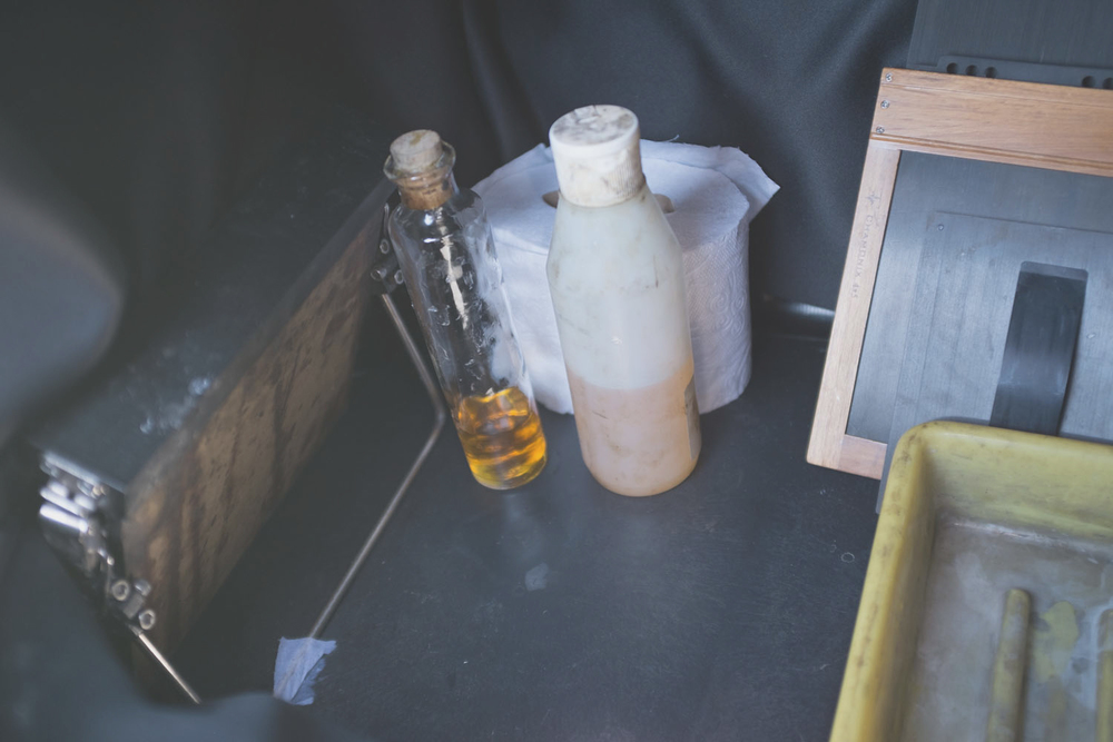 Inside the darkbox. From left to right is the silver tank (has water and silver nitrate in it), a bottle with collodion, developer, paper for wiping off the excess silver, a plate holder for 4x5 plates and - on the right - a tray for catching developer.