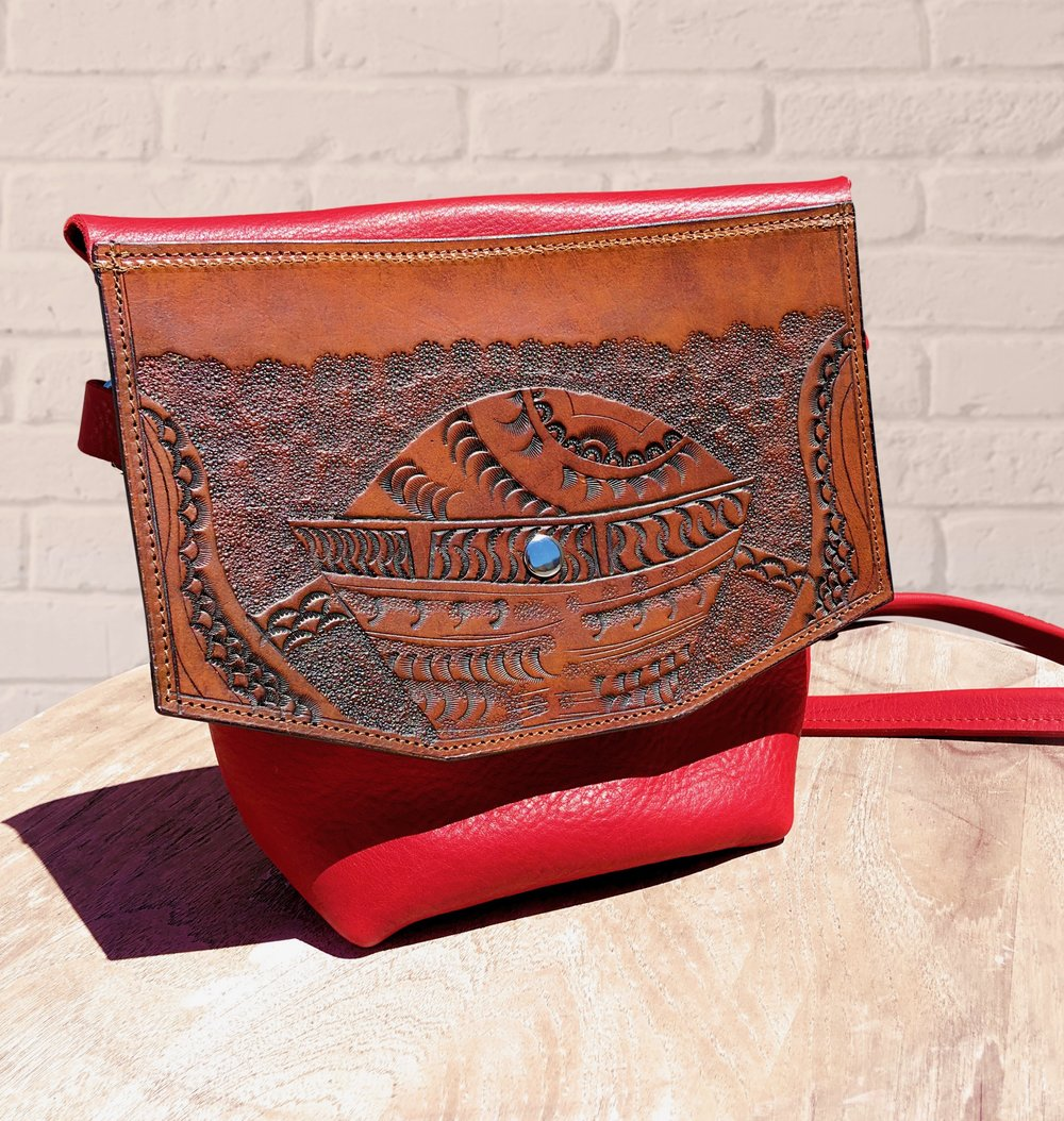 Red Tooled purse with a spaceship on it.  Made from soft red leather and features an interior pocket, adjustable strap and snap closure.