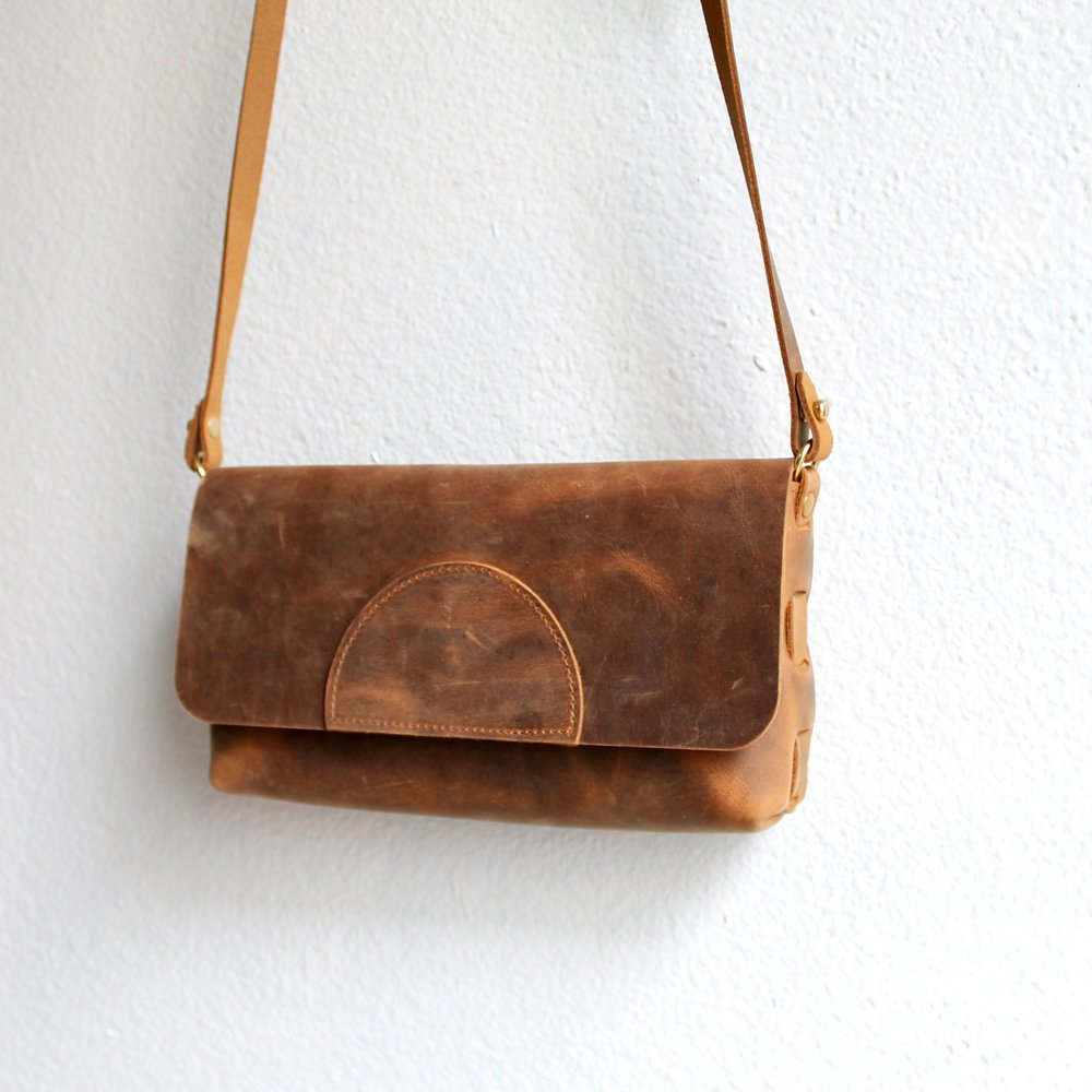 Our smallest bag, the Camino Convertible Clutch in Dusty Brown Cowhide. The strap easily detaches and the rings fold inwards to convert into a simple clutch for a night on the town. Easily fits a wallet, phone and keys, as well as any other bonus stuff you want to throw in there. Features our signature woven leather construction! I love this little guy.