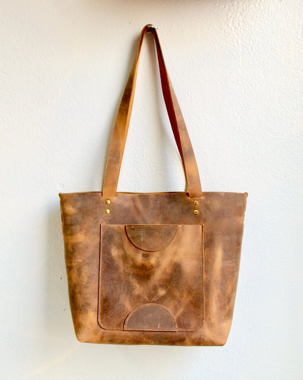 This leather is a waxed chrome tanned leather that has a distinct pull up effect.  When the leather is moved, the oils and waxes shift and lighten the area that they leave.