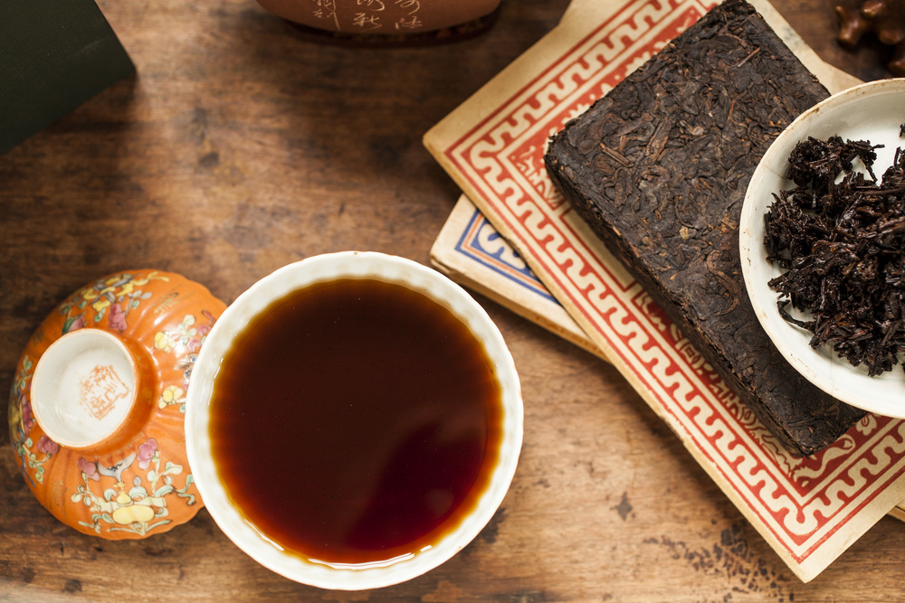 A masterfully brewed  Lotus Brick 2000  highlights the red brew and dark wet leaf of this pu-erh tea.
