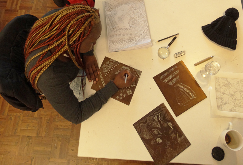 Ayel Akot surrounded by artwork and preparatory sketches