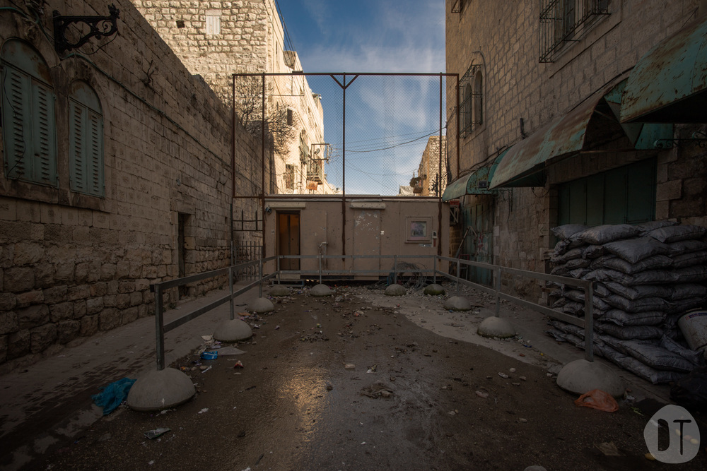 An IDF checkpoint at an entrance to Al-Shuhada Street, Hebron - only residents and tourists are allowed to pass.