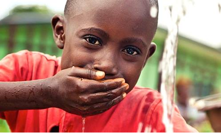 A Rwandan child, enjoying our gift of clean water!