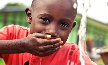 A Rwandan child, enjoying our gift of clean water!