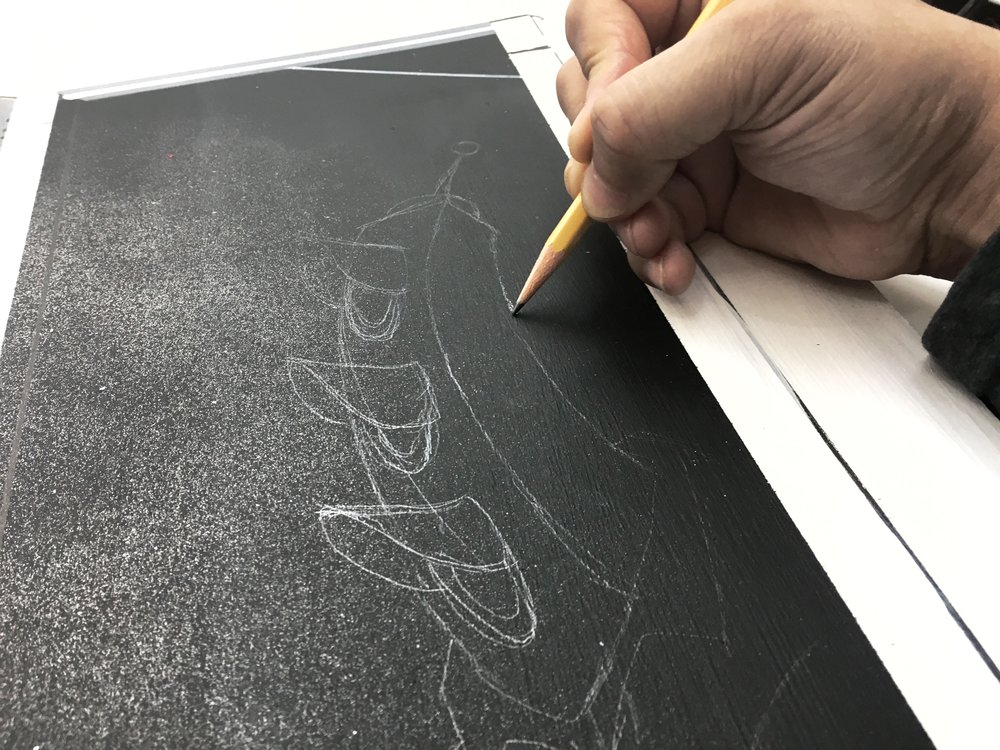 Drawing with pencil over black paint. You have to get the reflected light just right to see what your doing. I guess my camera can pick it up as well.