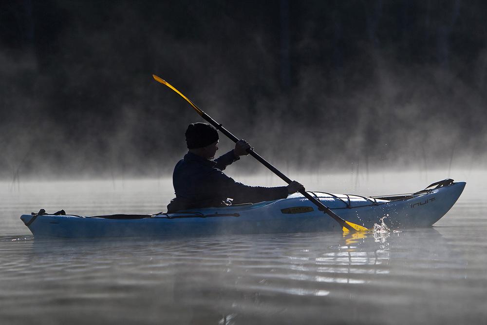 Scott Heister kayaking through the morning mist on Bruin Lake at the Pinckney Recreation Area, Michigan.