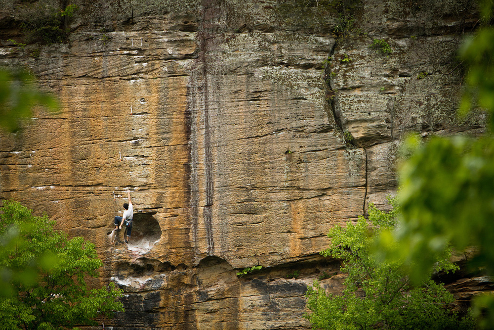 Rock climber shaking it out on Banshee, 5.11c, in Kentucky's Red River Gorge.