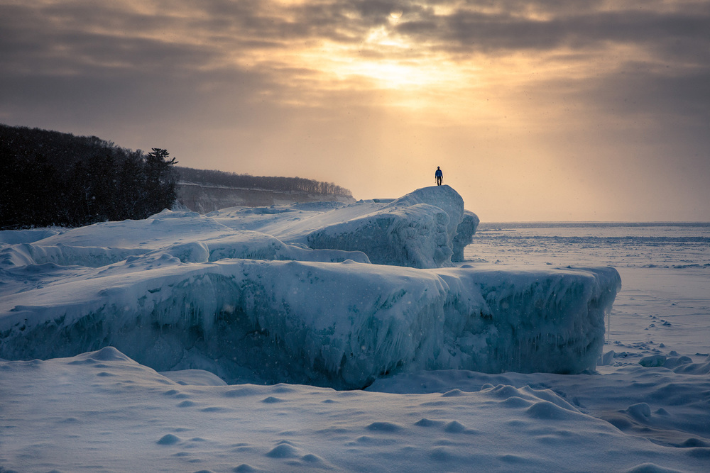 An ice climber stands on large boulders of ice, silhouetted against the evening sky along the frozen shore of Lake Superior, Michigan.