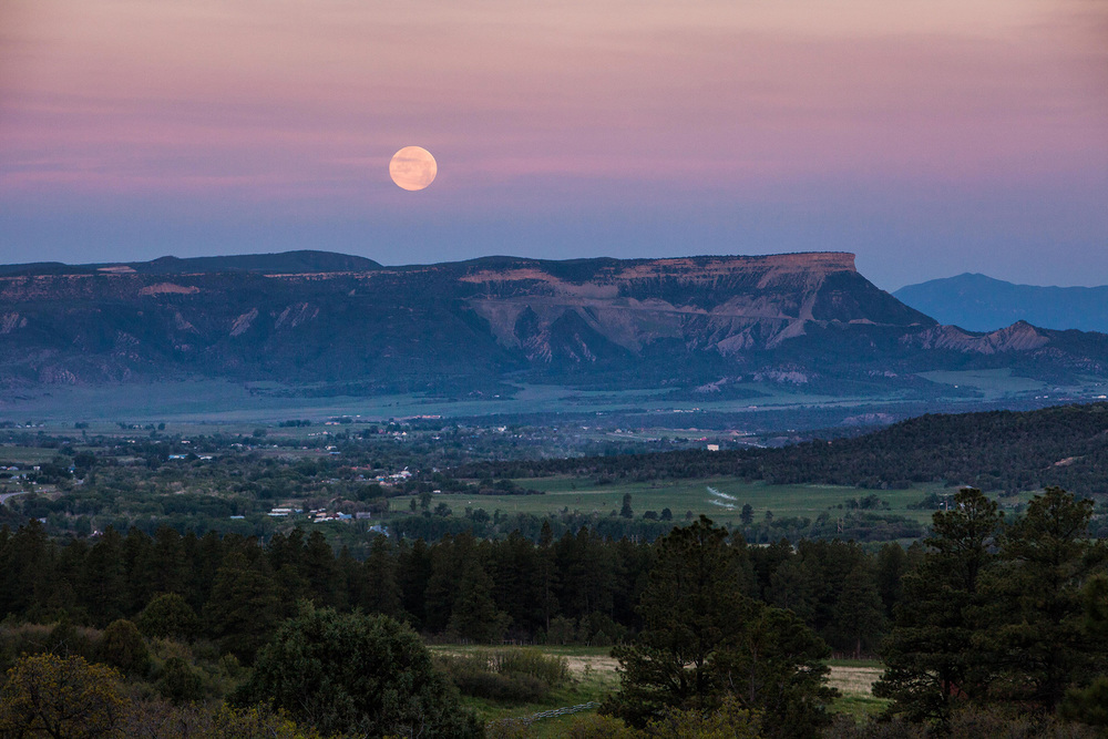 The moon sets over Mesa Verde National Park, while a light mist rolls through Mancos Valley.