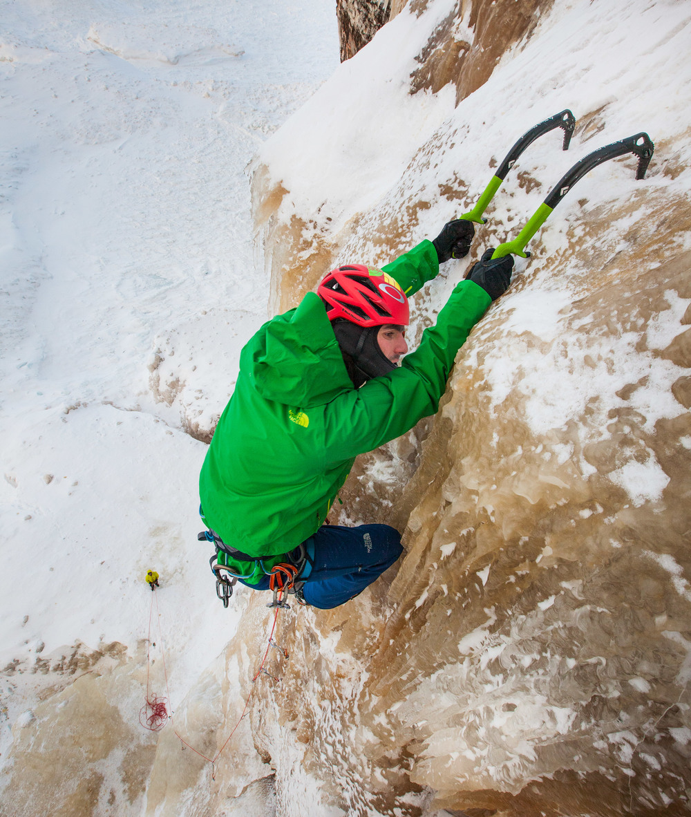 """North Face Athlete and Michigan-born climber Sam Elias ascends a sketchy lead on """"Fallen Feather,"""" on the frozen shore of Lake Superior."""