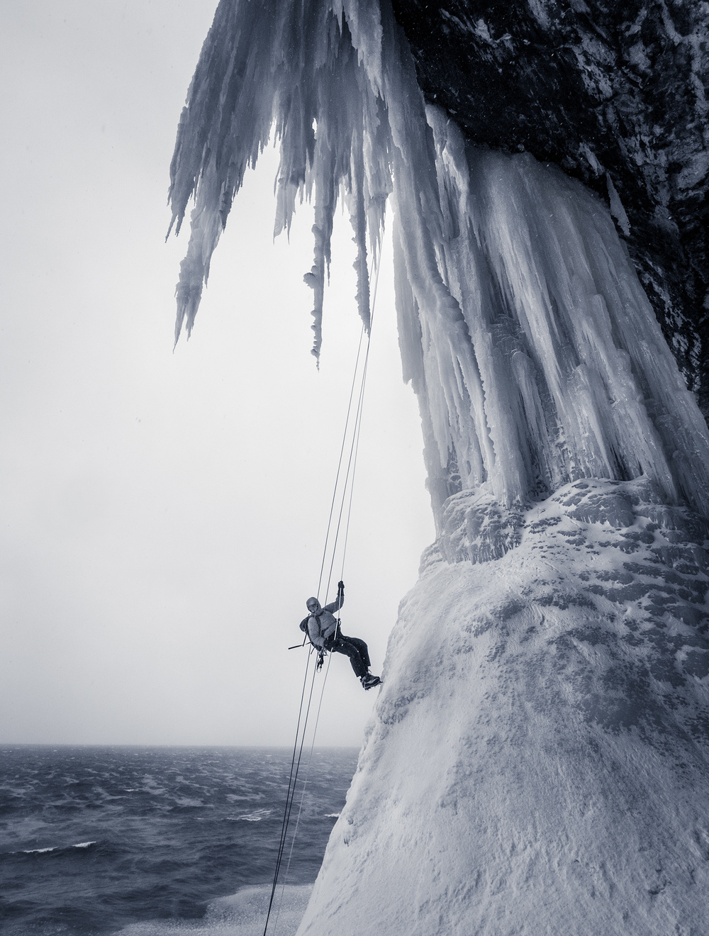 An ice climber rappels down Dairyland over the open water of Lake Superior.