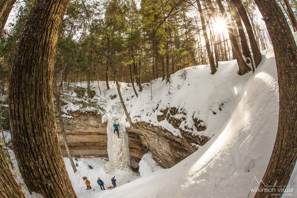 Some ice climbers practice top roping on a sunny day in the woods of Northern Michigan.