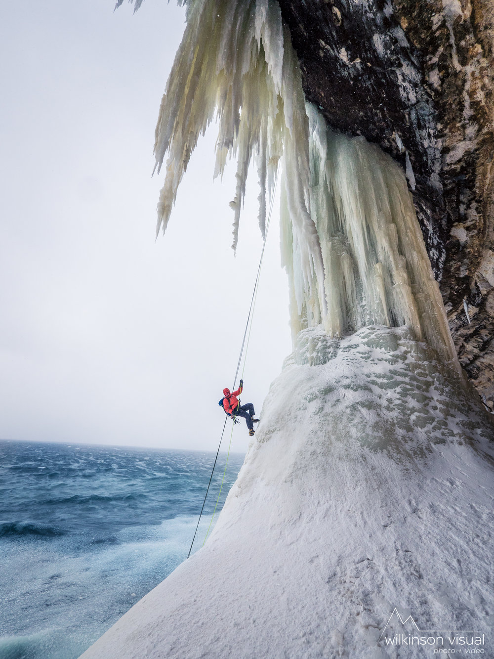 "Erik Olsen rappels down ""Dairyland"" with open water from Lake Superior crashing below. Pictured Rocks National Lakeshore, Michigan."