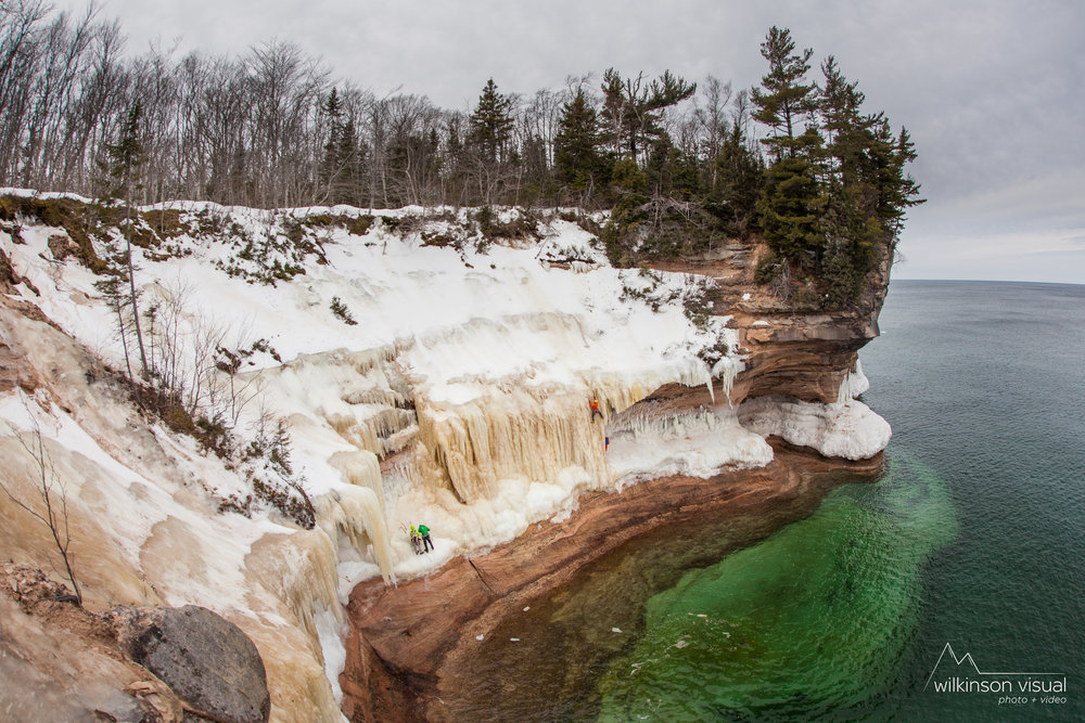 Two teams climb in the Singing in the Rain area along Pictured Rocks National Lakeshore in Northern Michigan. The climber in red is Angela VanWiemeersch.