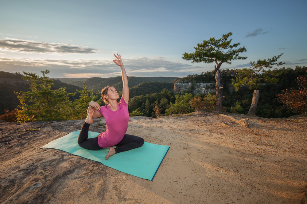 A model practices yoga during sunset in Kentucky's Red River Gorge.