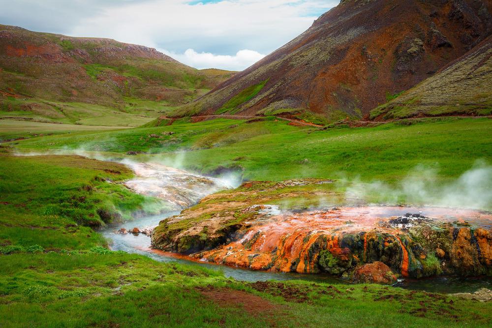 Heiße Quelle schlängelt sich durch sattes Grün