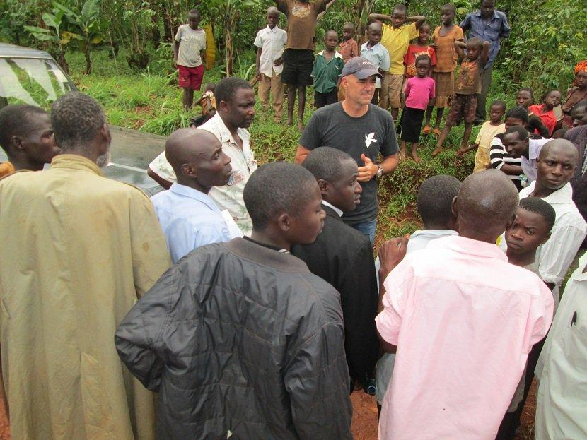 Accompanied by Trinity Children's Centre founder Romans Serunjogi, Travel Channel host Todd Carmichael negotiates with local farmers at a coffee farm in Bulago, Uganda.