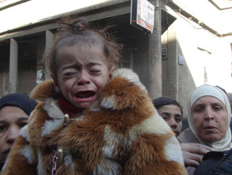 A malnourished child weeps on Yarmouk's main street in February 2014. © UNRWA Photo by Rami Al Sayed
