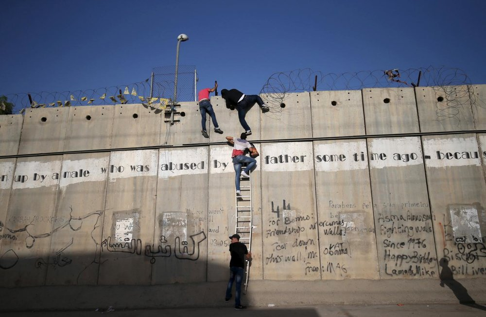Palestinians climb the Separation Wall to attend prayers. June, 2015