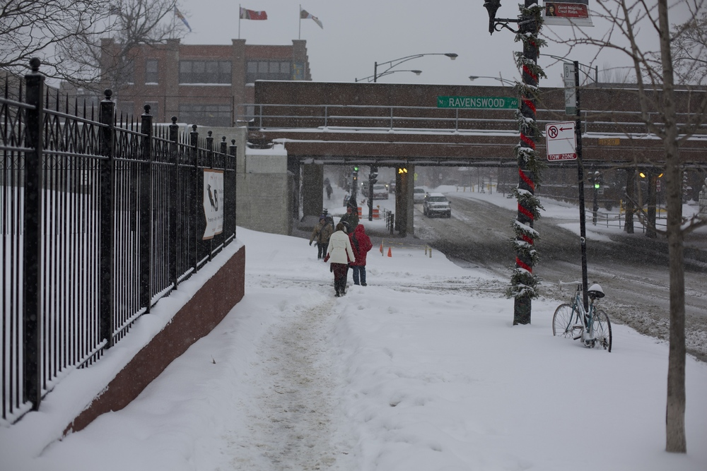 Commuters trudge through the snow near ravenswood, forging their own path when shoveling is neglected.
