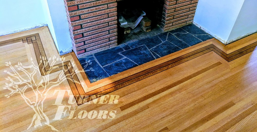 A top nail strip hardwood floor in Surrey, including a custom stained border.