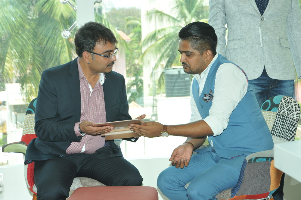 Mr. Anil Sanoria explaining Hardik Gandhi about the user interface of the app TOUCH.