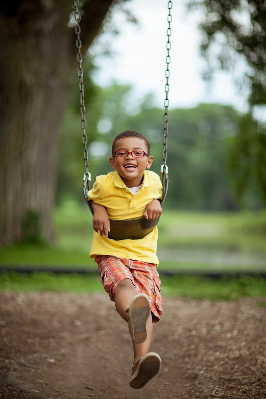 child's portrait on a swing set