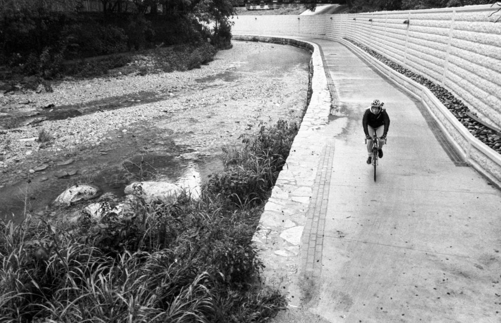 A cyclist bikes towards the camera at a river path in Austin, TX.