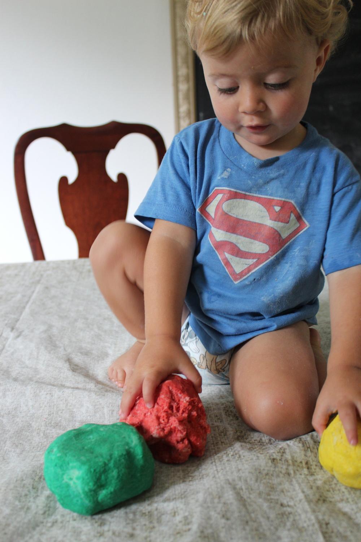 Diaper baby modeling the playdough.