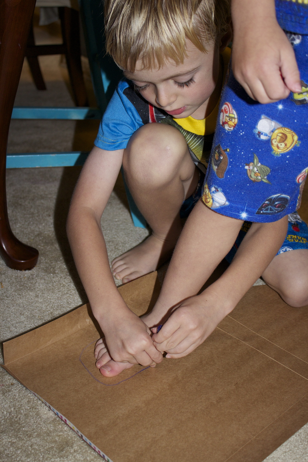 Tracing feet on cardboard.