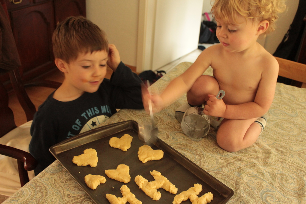 Shaping the cookies and smashing them with measuring cups.