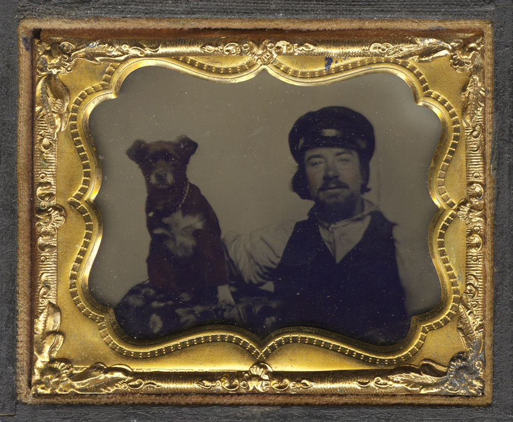 Portrait of a Man Next to His Dog who is Seated on a Small Table