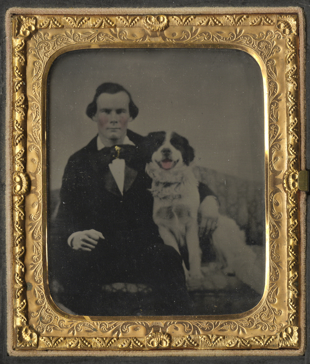 A Man and His Dog Seated Together on a Settee