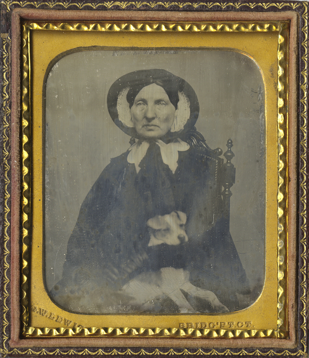 Portrait of a Woman Wearing a Cloak and Hat, Holding a Small Dog on her Lap