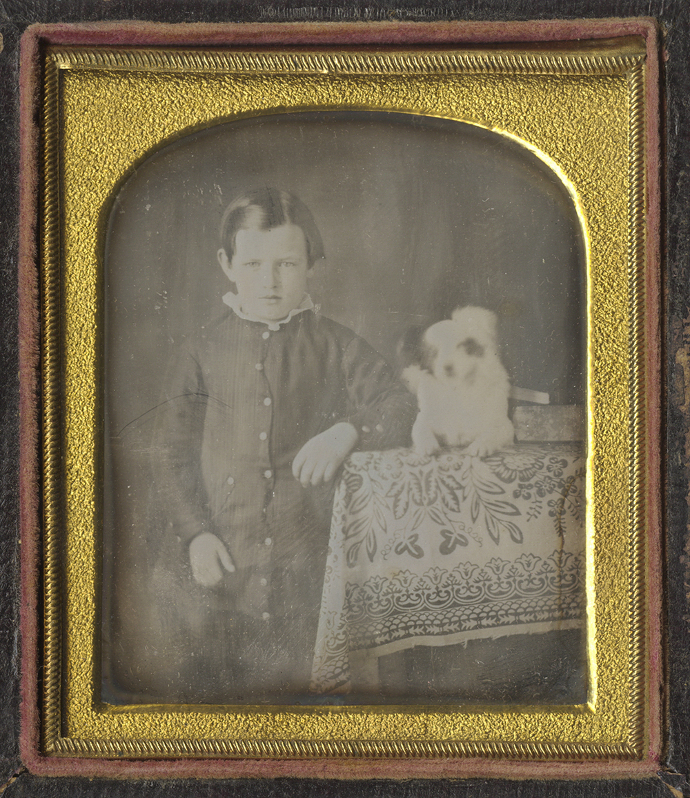 Young Boy Standing Beside his White Dog, Who Sits on a Table with a Patterned Cloth