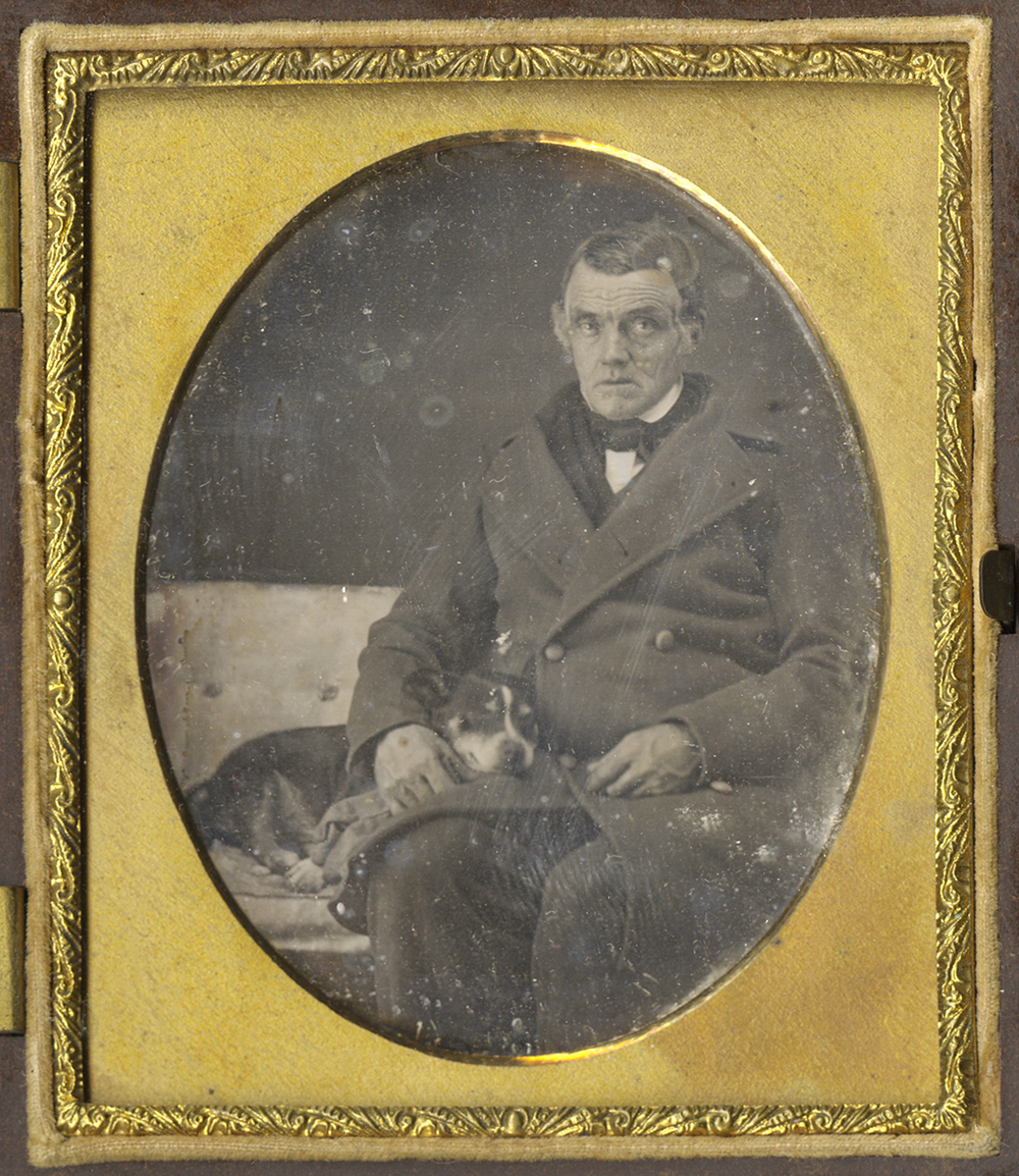 Gentleman Wearing an Overcoat Seated Next to his Small Dog