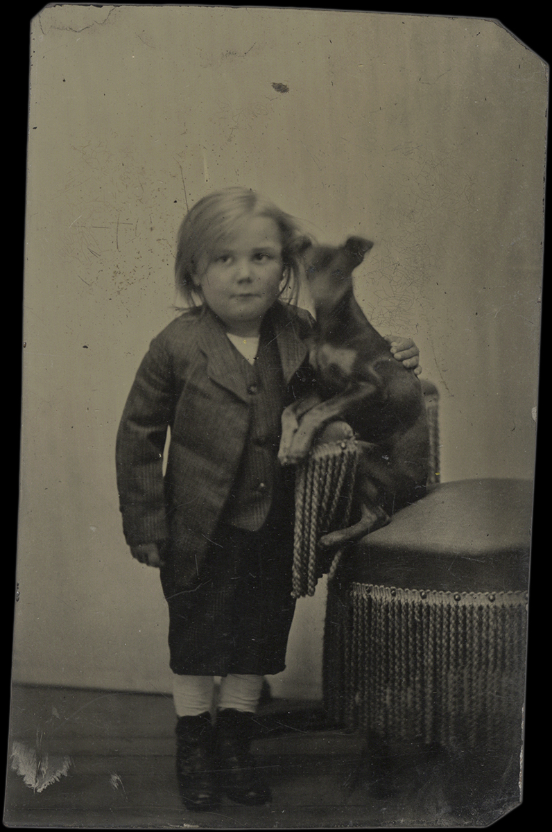 Little Boy Standing with his Arm Around his Dog