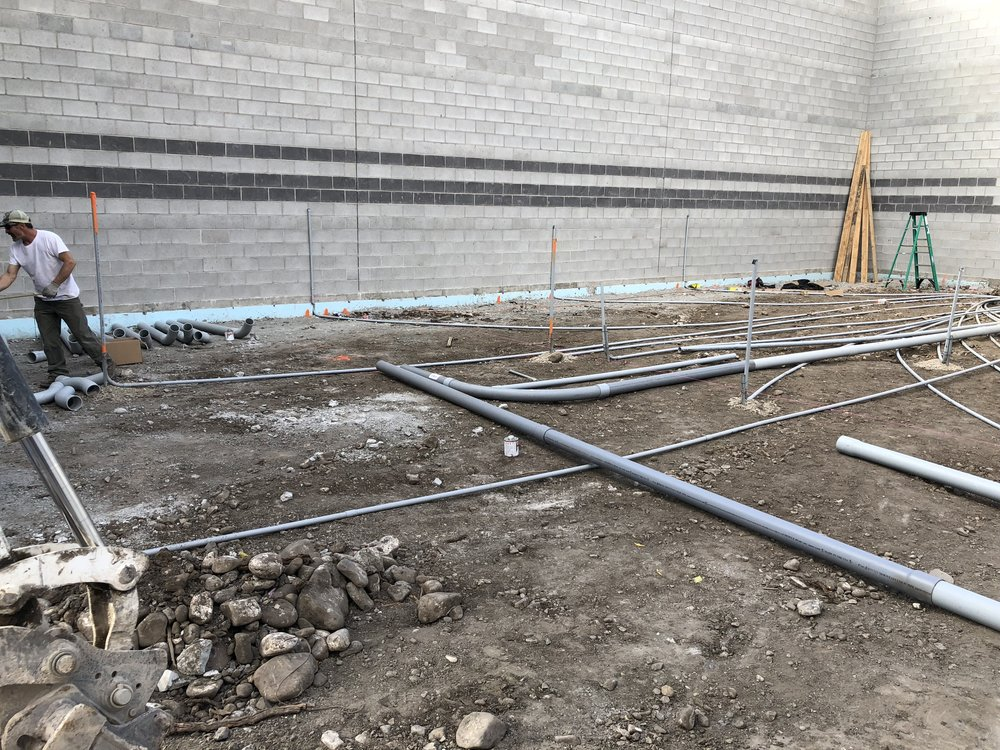 "The underground work continues. The smaller conduit is for power (many home-runs), the larger 4"" pipe is for audio connections."