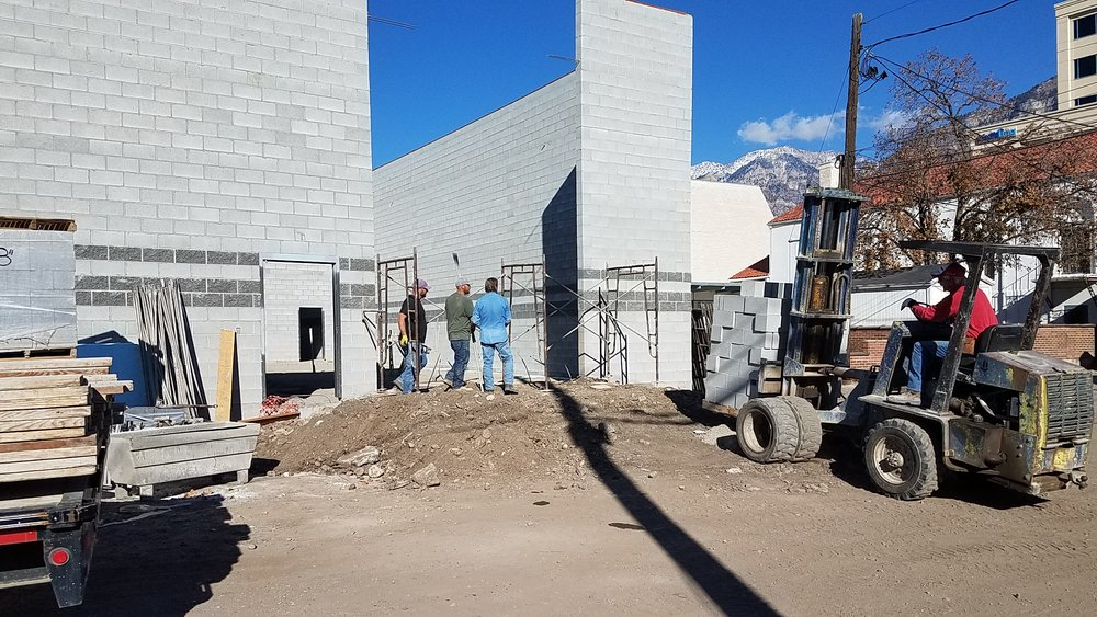 With the gravel in place and the slab set to be poured, the masons showed up to fill the large hole in the back of the building.