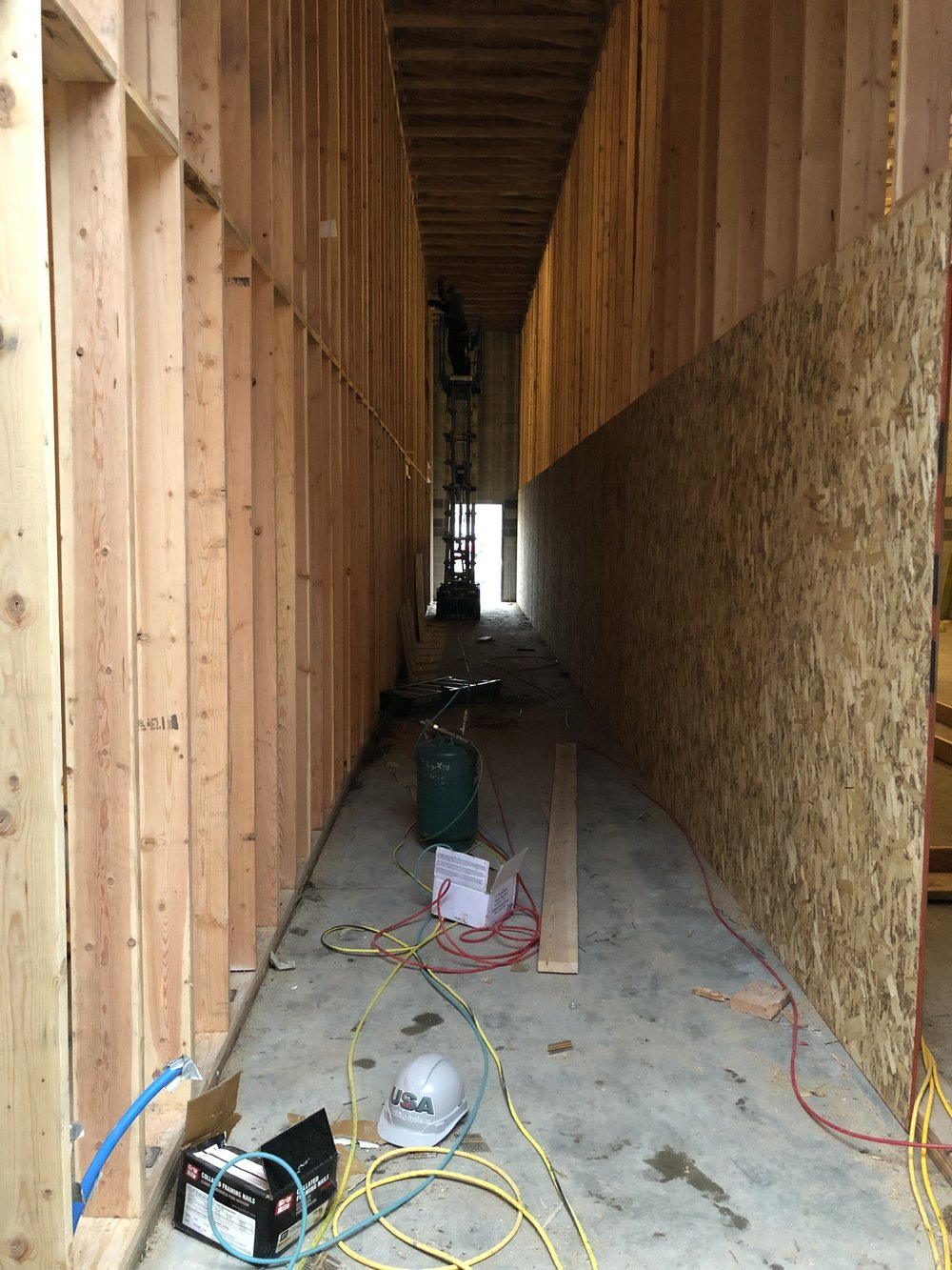 Looking down the hallway between studios toward the back door. OSB sheeting going up on the walls.
