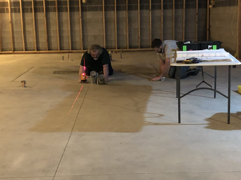 Tony Brett flew in on January 7 and early on the 8th got to work. First he used a laser level to establish and layout the center line of studio 1 and then set some points to show where the walls would sit.