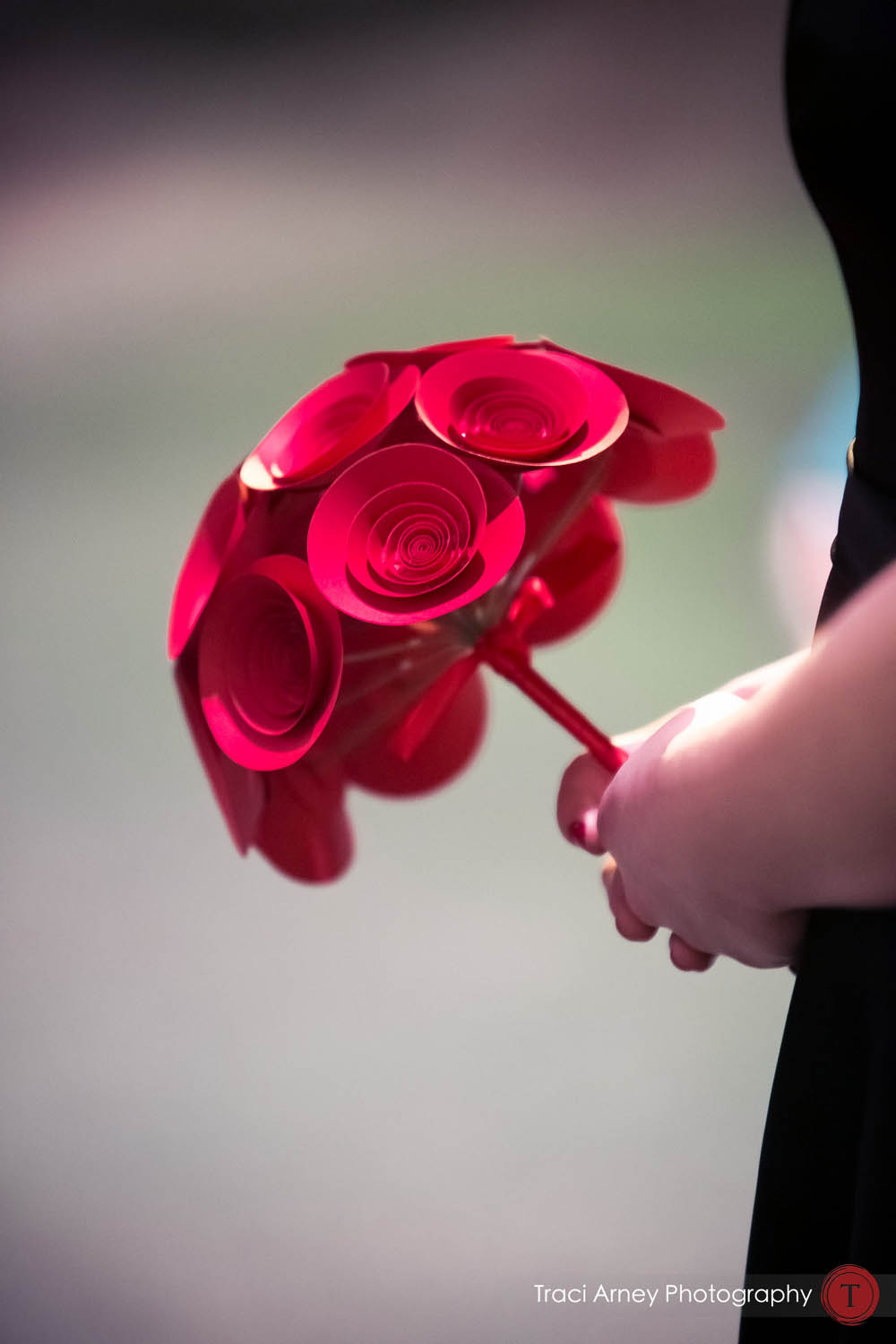 The bridesmaids carried medium paper flower bouquets in classic red.  Image courtesy of  Traci Arney Photography .